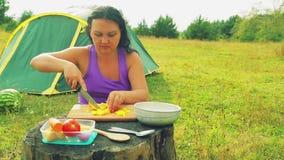 在帐篷附近的一名妇女在dervy桌面染黄胡椒入与一把刀子的小立方体在一个木板 股票录像