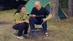 在帐篷附近的一名妇女油煎在栅格烤鱼的 人在她旁边接近,坐下并且击碎格栅 股票录像