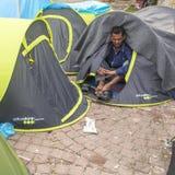 在帐篷附近的战争难民 更多比半的是从叙利亚的移民,但是有从其他国家的难民 免版税库存照片