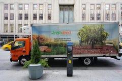 在帝国大厦前面的一辆新鲜的直接送货卡车在纽约 免版税库存图片