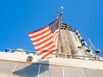 在帝国大厦顶部的美国国旗在纽约 库存图片
