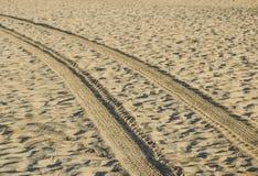 在带领入海的金黄沙子的轨道在日落 免版税库存照片