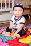 在席子和帽子的一个俏丽的婴孩供以座位的镶边衬衣在屋子里 库存照片