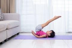 在席子的亚洲中国小女孩实践的瑜伽姿势 免版税库存图片