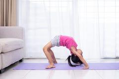 在席子的亚洲中国小女孩实践的瑜伽姿势 库存照片