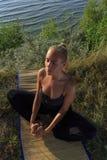 在席子的美好的少妇实践的瑜伽户外在草的河岸 免版税库存图片