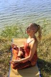 在席子的美好的少妇实践的瑜伽户外在草的河岸 库存图片