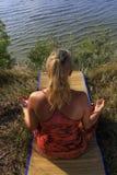 在席子的美好的少妇实践的瑜伽户外在草的河岸 免版税库存照片