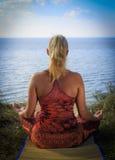在席子的美好的少妇实践的瑜伽户外在草的河岸 免版税图库摄影