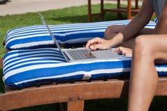 在席子deckchair的妇女感人的膝上型计算机 图库摄影