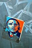 在帮会街道画的被抓的和被撕毁的奥巴马贴纸 免版税图库摄影