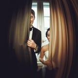 在帷幕后半掩藏的微笑的新婚佳偶 库存图片