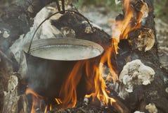 在常礼帽的开水在篝火 免版税图库摄影
