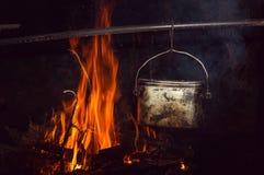 在常礼帽的开水在篝火 免版税库存照片