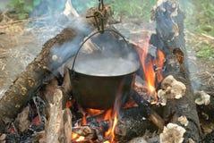 在常礼帽的开水在篝火 库存照片