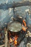 在常礼帽的开水在篝火 库存图片
