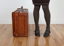在常设手提箱葡萄酒妇女附近 免版税库存图片