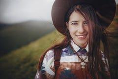 在帽子的时髦的旅客女孩画象有在山的背包的 库存图片