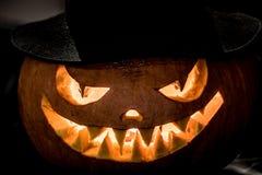 在帽子的邪恶的万圣夜南瓜头在黑暗的背景 免版税库存照片