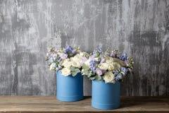 在帽子箱子蓝色的两朵花花束 站立在一张木桌上 在背景老灰色墙壁艺术 复制空间 库存图片