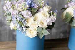 在帽子箱子蓝色的两朵花花束 站立在一张木桌上 在背景老灰色墙壁艺术 复制空间 免版税库存照片