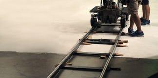 在幕后生产队设置移动式摄影车轨道 免版税图库摄影