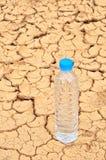 在干旱的背景的饮用水瓶 免版税图库摄影