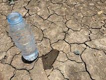 在干燥和破裂的地面的一个水瓶 免版税库存照片