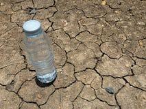 在干燥和破裂的地面的水瓶 库存图片