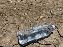 在干燥和破裂的地面的水瓶 库存照片