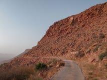在干燥岩石山坡的老路在葡萄酒日落光的沙漠 免版税库存图片