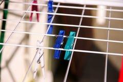 在干燥机架,选择聚焦的布料晒衣夹 在晒衣绳的五颜六色的塑料晒衣夹 免版税图库摄影