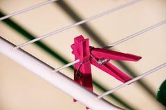 在干燥机架,选择聚焦的布料晒衣夹 在晒衣绳的五颜六色的塑料晒衣夹 免版税库存照片