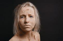 在干燥破裂的泥盖的被弄乱的妇女 库存图片