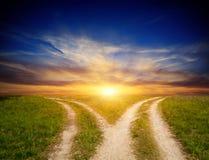 在干草原的叉子路在日落天空背景 库存照片