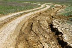 在干草原,越野驱动的未铺砌的打破的干燥土乡下公路 免版税图库摄影