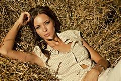 在干草堆的美丽的女孩 免版税库存照片