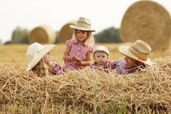在干草堆的年轻家庭牛仔帽的 免版税库存图片