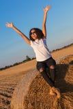 在干草捆的混合的族种非裔美国人的女孩青少年的太阳镜 库存照片