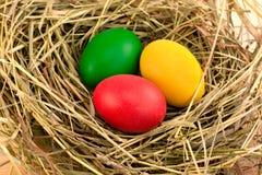 在干草的三个被绘的复活节彩蛋 库存照片
