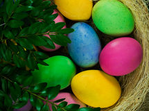 在干草的五颜六色的复活节彩蛋在柳条筐 库存图片