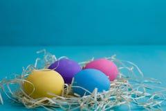 在干草的多彩多姿的复活节彩蛋在蓝色背景,关闭, co 免版税库存图片