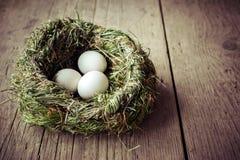 在干草的有机白鸡蛋筑巢在木桌上 免版税库存图片