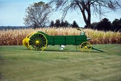 在干草茎前面的绿色推车 库存照片