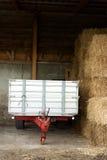 在干草谷仓停放的农厂拖车 免版税库存照片