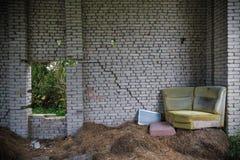 在干草顶部的腐朽的老沙发 免版税库存照片