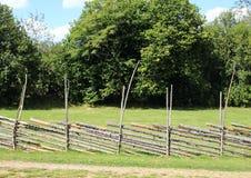在干草领域的农村简单的木篱芭 库存图片