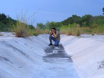 在干水路的男性摄影师射击照相机 免版税图库摄影