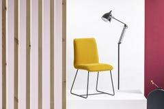 在平台和高黑工业灯的时髦黄色椅子在它后在与紫色和木墙壁的白色和明亮的内部 免版税库存图片