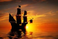 在平安的海洋的老古老海盗船日落的 库存照片